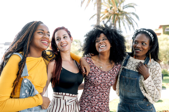 Friendly multiracial group of female friends cuddling on street while spending weekend in summer together