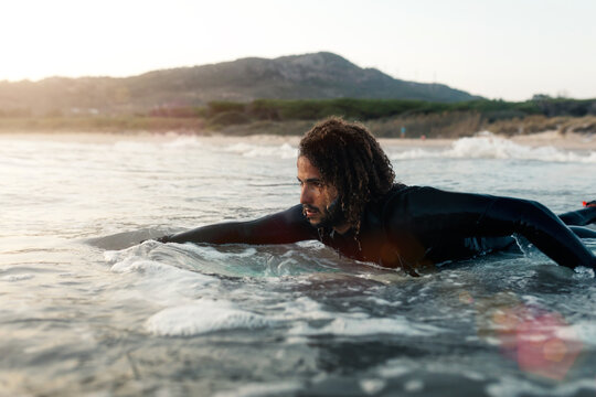 Serious surfer with curly hair in black wetsuit looking at coming wave while swimming on board in sea at sunset