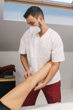 Side view of male therapist stretching legs of female patient lying on table during physiotherapy massage in clinic