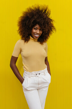 Portrait of a curly haired black woman looking at camera in front of a yellow background