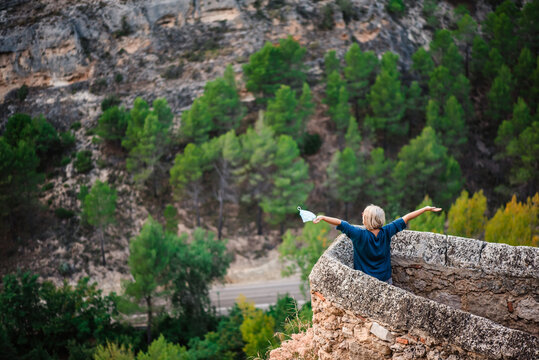 From above back view of female tourist with map standing near stone border of medieval fortress against rocky mountain slope with green forest and enjoying freedom while visiting Cuenca town in Spain