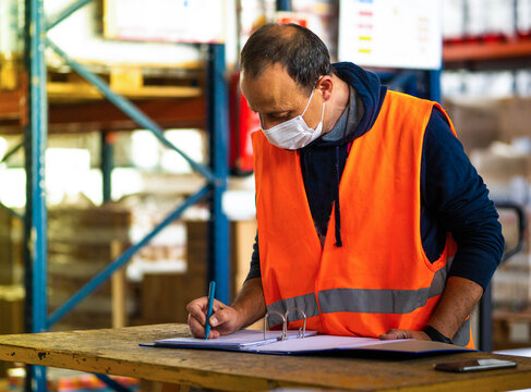 Side view adult worker wearing uniform and protective face mask writing on clipboard while working in spacious storehouse