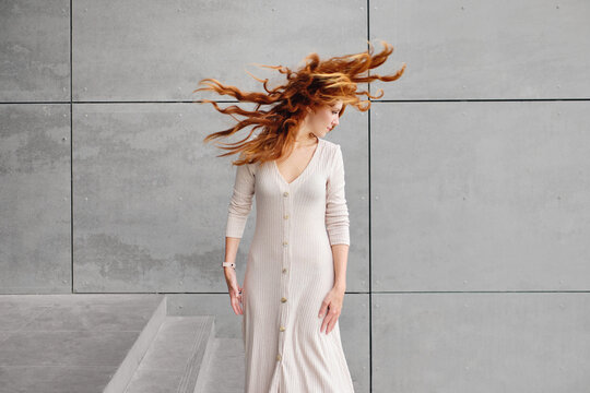 Female with long red hair fluttering in wind standing against gray concrete wall on street