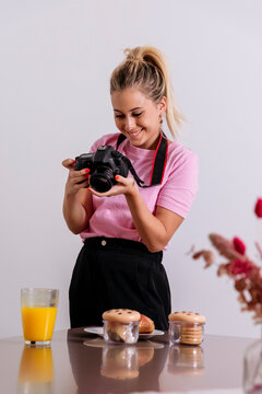 Delighted female photographer with professional photo camera looking at pictures taken during photoshoot of food in studio
