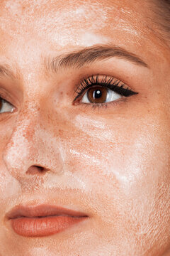 Cropped young beautiful woman with healthy skin taking care of face with cream isolated on gray background