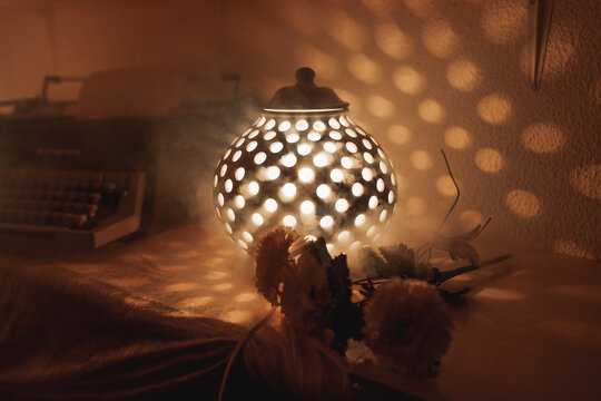 Vintage lamp with holes on table with old typewriter illuminating dark cozy room