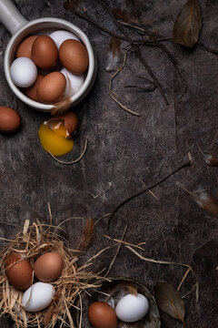Top view of cracked and whole chicken eggs of white and brown colors arranged on messy surface with feathers