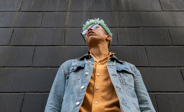 From below of young African American male model with blue hair and in casual outfit standing near urban building in city and looking away
