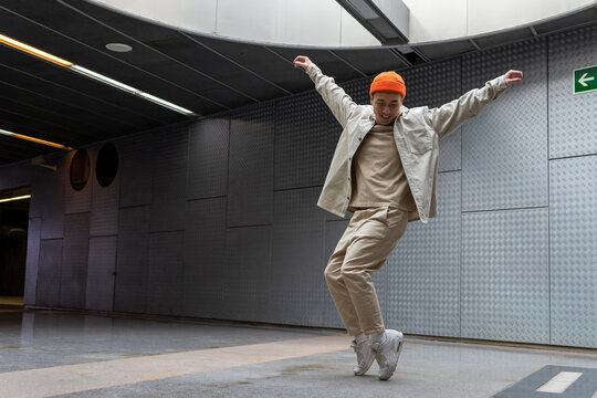 Full body happy young Asian male wearing light casual outfit and orange hat standing with arms outstretched on tiptoes and looking down with smile
