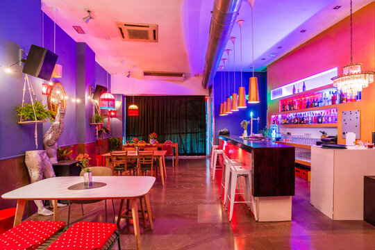 Interior of empty stylish bar with neon lights and modern design decorated with flowers and lamps