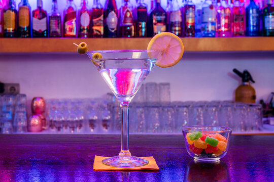 Glass of alcoholic martini cocktail made with gin and vermouth decorated with slice of lemon and olives served with cup of marmalade