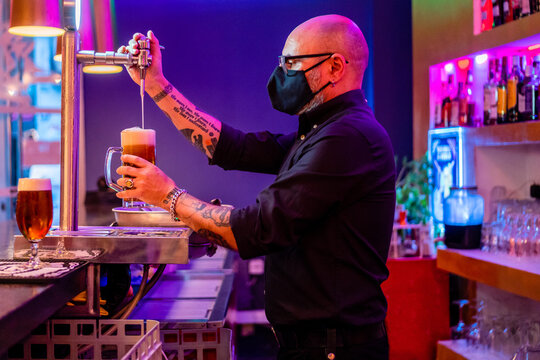Side view of serious barkeeper in eyeglasses pouring beer into glass while working in bar during coronavirus pandemic