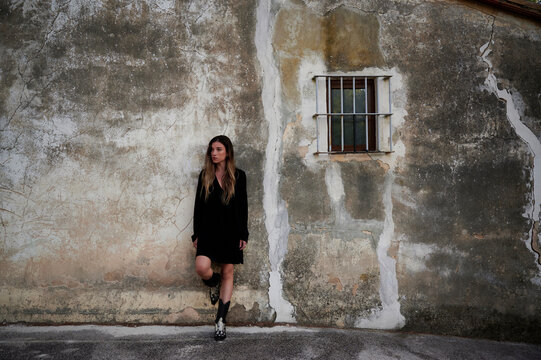 Full body of young female in casual black dress and boots leaning back against shabby stone wall of aged building with small window