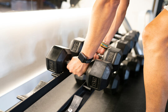 Anonymous person with smart watch taking heavy dumbbells from rack during weightlifting workout in gym