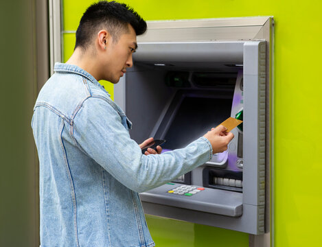 Side view of young Asian male with smartphone in hand inserting card into ATM terminal for withdrawing cash on city street