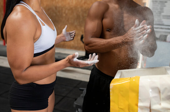 Unrecognizable crop diverse athletes with strong bodies using chalk before weightlifting workout in modern gym