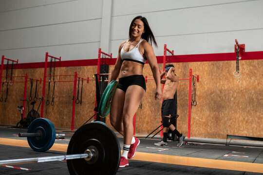 Low angle of delighted female weightlifter preparing barbell for doing exercises during training in gym