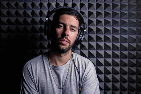 Stylish male singer wearing headphones standing in recording studio on background of soundproof acoustic panel and looking at camera