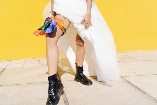 Crop anonymous bride wearing white dress with boots and LGBT flag tied as garter on leg standing on sunny street
