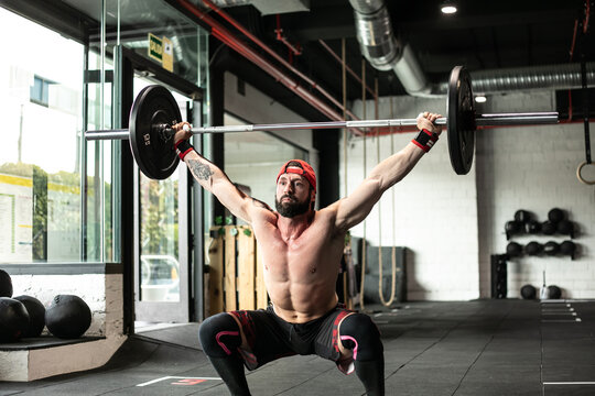 Muscular focused shirtless male athlete doing clean and jerk exercise with barbell during weightlifting training in gym looking away