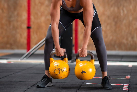 Crop unrecognizable female athlete in sports clothes lifting heavy weights during functional training in gym