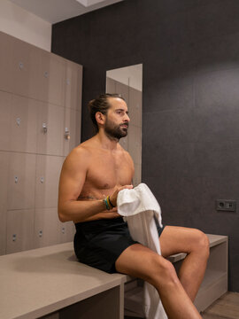 Side view of bearded man without shirt resting in gym locker room