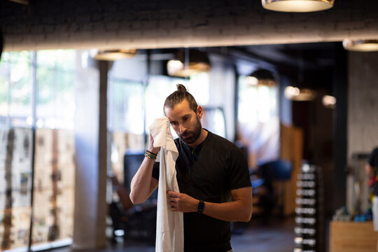 Bearded adult sportsman wiping sweat from forehead with towel during fitness workout in modern gym