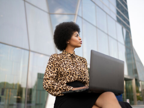 From below side view of busy African American female with afro sitting on bench with computer typing text while working remotely near glass building