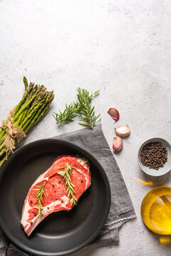 Top view of uncooked raw t bone steak garnished with rosemary and black pepper peas placed in frying pan on table in kitchen
