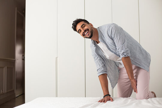 Cheerful male wearing domestic clothes making soft bed in cozy bedroom after awakening in morning