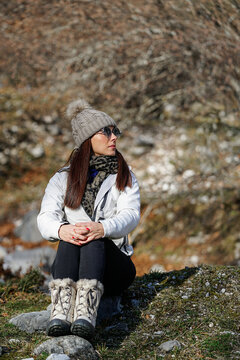 Female tourist in warm boots and coat sitting on ground in woods on sunny day while embracing knees and relaxing during trekking in winter