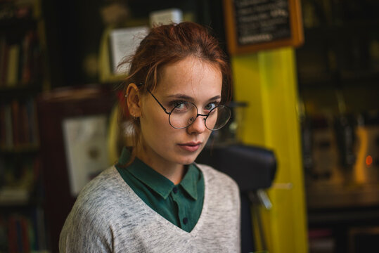Serious smart female wearing casual clothes and eyeglasses standing in cozy library on background of bookshelves and looking at camera