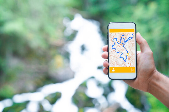 Cropped unrecognizable man traveler using smartphone browsing on map app standing on slope of amazing landscape of green forest with fast river