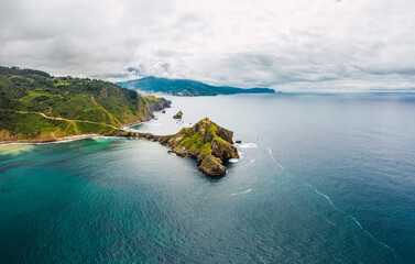Drone view of paving stone way leading along stone bridge and ridge of rocky hill to lonely house on island Gaztelugatxe surrounded by tranquil sea water under cloudy sky in Basque Country Fotobehang