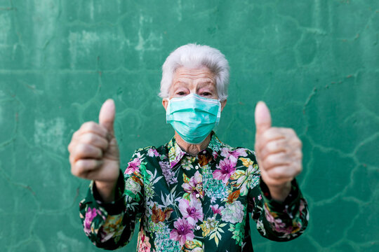 Optimistic elderly lady in stylish colorful outfit and protective mask for coronavirus prevention looking at camera and showing thumbs up gesture against green wall