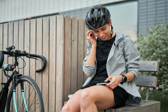 Woman courier with phone in his hands sits on bench next to bicycle on background of building on summer day