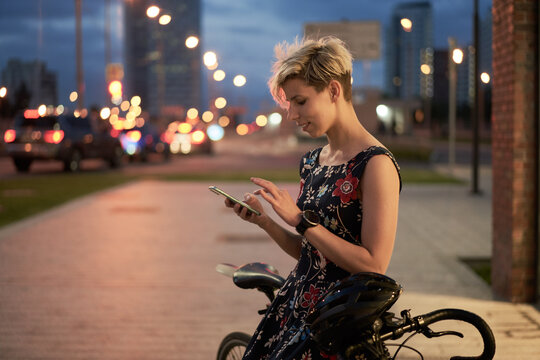Young woman with phone in hand sits near bicycle at night city