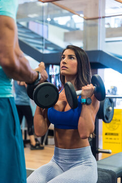 Strong female athlete doing exercises with dumbbells with support of personal coach during workout in gym