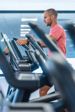 Side view of handsome male doing exercises on elliptical machine during cardio workout in modern sports club