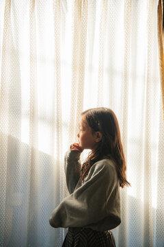 窓の外を見つめる少女