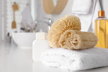 Wall Mural - Natural loofah sponges and towel on table in bathroom. Space for text