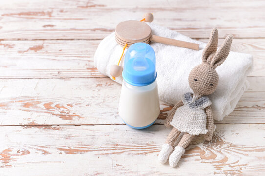 Bottle of milk for baby with toys and towel on white wooden background