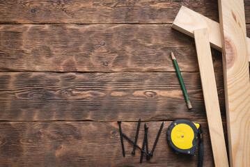 Fototapeta Screws, meter, pencil and wooden bars on the carpenter workbench background flat lay. obraz