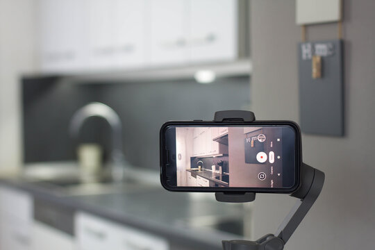 Mobile phone recording a home video on a gimbal stabilizer.