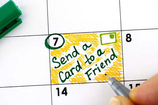 Woman fingers with pen writing reminder Send a Card to a Friend Day in calendar