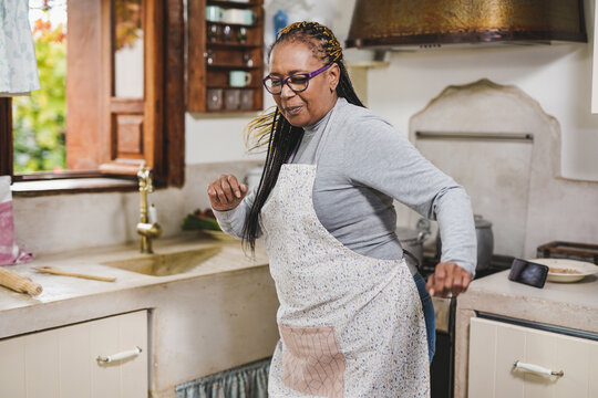 African senior woman have fun in vintage kitchen and dancing to smartphone playlist music