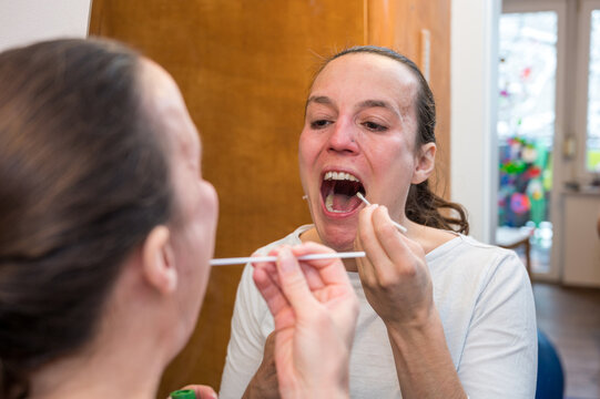 Woman using an oropharyngeal swab for covid 19 detection.