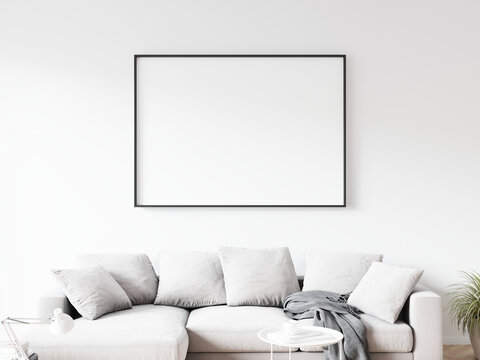 Horizontally oriented rectangular picture frame with thin black border hanging on white wall above sofa in living room. 3D illustration.