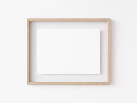 Empty horizontally oriented rectangular light wood picture frame hanging on white wall. 3D Illustration.
