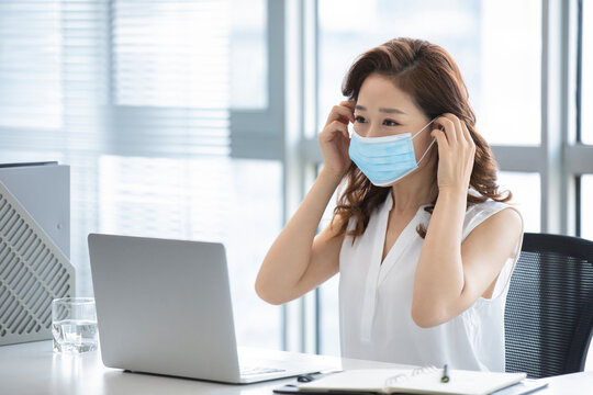 Young businesswoman wearing surgical mask in office